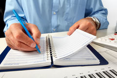 Hand writing in notepad. Businessman working in office Stock Images