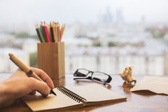 Hand writing in notepad closeup. Closeup of hand writing in spiral notepad placed on wooden windowsill with glasses, colorful pencils and other items Royalty Free Stock Photography