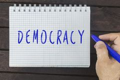Hand writing on notepad: Democracy. Human hand writing on notepad inscription: Democracy royalty free stock images