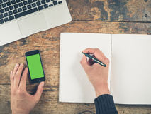 Hand writing in notepad by laptop and smart phone Royalty Free Stock Photography