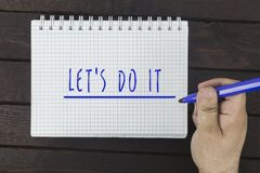 Hand writing on notepad: Let`s do it Royalty Free Stock Image