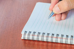 Hand writing notes book on wood table, selective focus. Royalty Free Stock Photography
