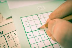 Hand is writing numbers in grid of popular logic game sudoku Stock Photography
