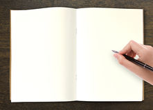 Hand writing in open book on table. Hand writing in open book on wood table Royalty Free Stock Images