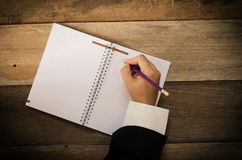 Hand writing in open notebook on table. Stock Photography