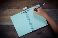 Hand writing in open notebook on table. Royalty Free Stock Photography