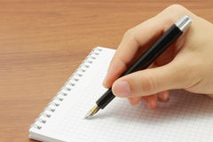 Hand writing in open notepad. On table Stock Photos