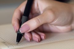 The hand is writing in a notebook Royalty Free Stock Photography