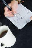 Hand writing on paper calendar next to coffee mug Stock Photos