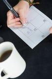 Hand writing on paper calendar next to coffee mug. Hand writing on paper calendar date 21 next to coffee mug Stock Photos