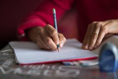 Hand writing on paper with pencil on desk. Selective focus on pencil, home interior, very shallow depth of field. Stock Images