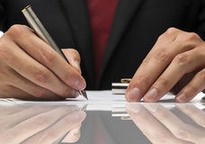 Hand writing a paper with reflection. Stock Images