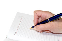 Hand writing with a pen, on a blank notebook Stock Photo