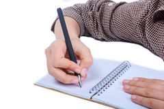 Hand writing with a pen. A child hand is writing with pen on a spiral notebook on white background Stock Photography
