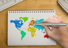 Hand writing with pen on Colorful Map on a notepad Stock Image