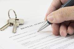 Hand is writing with a pen on a rental agreement document, house Royalty Free Stock Photography
