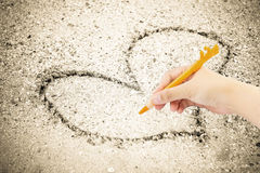 Hand writing with pen on sand Stock Photo