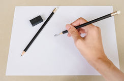 Hand writing by Pencil Eraser in white paper and Erase rubber on Desk Stock Photography