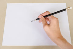 Hand writing by Pencil Eraser in white paper and Erase rubber on Desk Royalty Free Stock Image