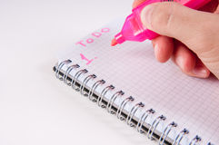 Hand writing by pink on empty notepad, white background Royalty Free Stock Image