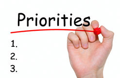 Hand writing Priorities with red marker on transparent wipe board. Hand writing Priorities with red marker on transparent wipe board Stock Photography