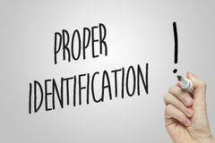 Hand writing proper identification. On grey background Royalty Free Stock Photography