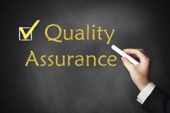 Hand writing quality assurance on chalkboard Stock Image