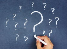 Hand writing question marks on blackboard. Human hand writing question marks on blackboard Royalty Free Stock Images