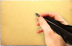 Hand writing with quill on old grungy postcard Stock Photo