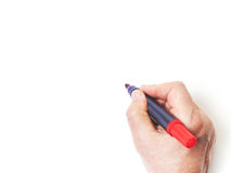 Hand writing with red marker on white background. Hand writing with red marker closeup view from above Royalty Free Stock Photo