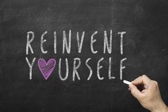Hand writing Reinvent Yourself Stock Photo