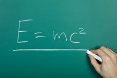 Hand writing relativity formula on blackboard Royalty Free Stock Photo