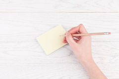 Hand writing on reminder notes with wood pencil Royalty Free Stock Images