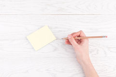 Hand writing on reminder notes with wood pencil. Woman hand writing on reminder notes with wood pencil on wooden table Stock Photo