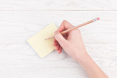 Hand writing on reminder notes with wood pencil. Woman hand writing on reminder notes with wood pencil on wooden table Stock Image