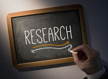 Hand writing Research on chalkboard. Hand writing the word research on black chalkboard Royalty Free Stock Photography