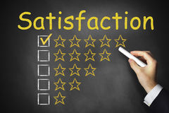 Hand writing satisfaction on black chalkboard stars Stock Photo