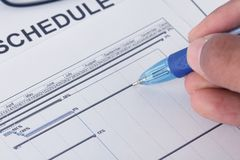Hand writing on schedule document with pen and gantt chart. Working with schedule royalty free stock images