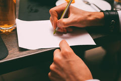 Hand writing on sheet in night club. Man's hand writing on sheet in night club Royalty Free Stock Images
