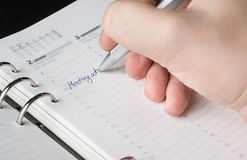 Hand writing with silver pen on open agenda Royalty Free Stock Photography