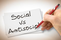 Hand writing Social Vs Antisocial with a pencil on a blank sheet - concept image.  stock photography