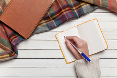 Hand writing something. Female hand writing something in to notebook Stock Images