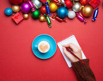 Hand writing something. In to the notebook near christmas toys stock photo