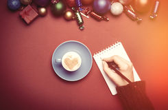Hand writing something in to the notebook near christmas toys. Stock Photography