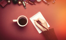 Hand writing something in to the notebook near christmas toys. Stock Photo