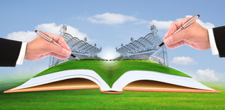 Hand writing stadium on green grass
