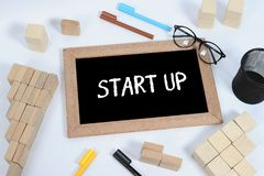 A hand writing `Start-Up` on blackboard. Blackboard, glasses, pen case and wood block stacking as step stair symbol of business stock image