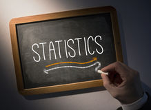Hand writing Statistics on chalkboard Royalty Free Stock Images