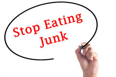 Hand writing Stop Eating Junk on transparent board.  royalty free stock images