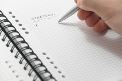 Hand writing strategy list on white notebook Stock Photography